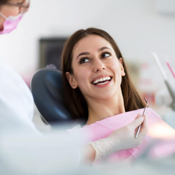 a young woman in the dental chair smiling and looking up at the dental hygienist