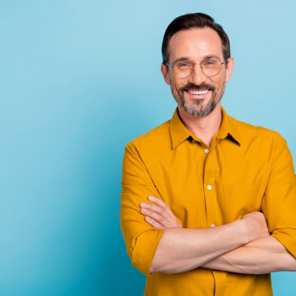 a middle aged man smiling with his arms crossed against a blue background