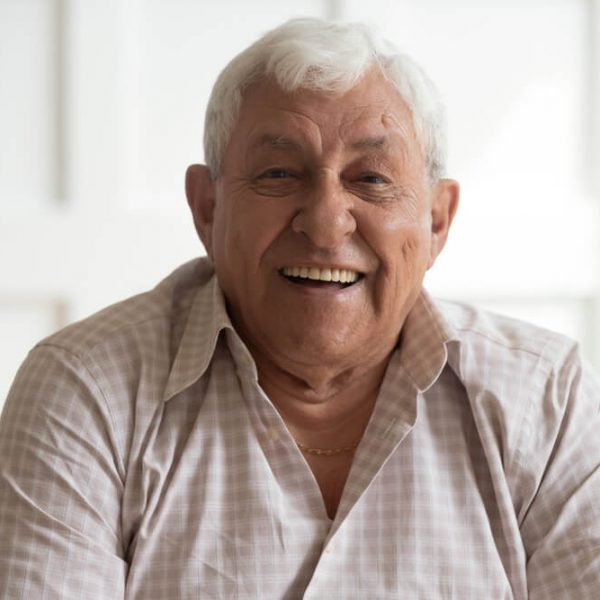 an older man smiling while sitting on the couch