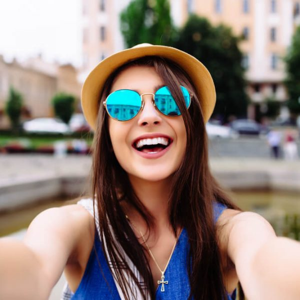 a young woman taking a fun selfie while outside smiling