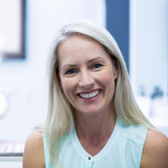 A middle aged woman smiling while at the dentist's office