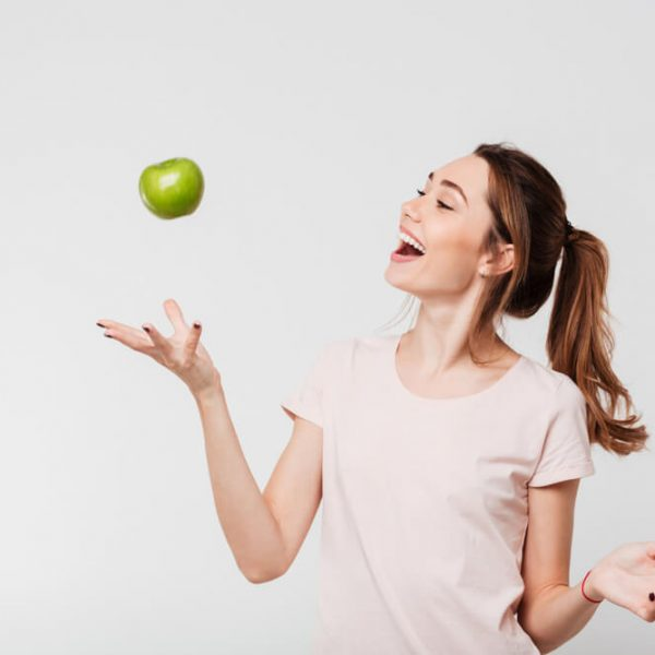 a young woman laughing while tossing up a green apple